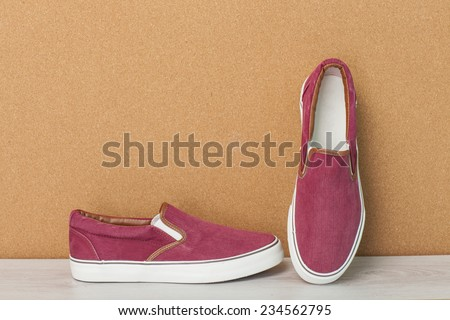 Red Sneaker on a Wood Background, slip-on shoes - stock photo