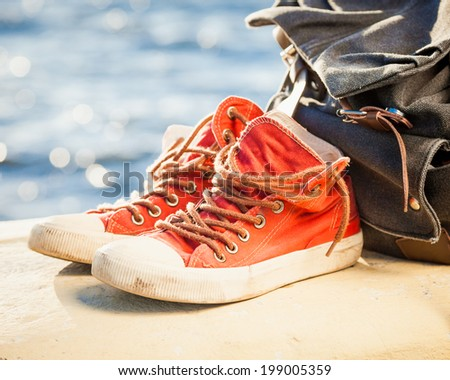 red sneakers and backpack on seascape  - stock photo