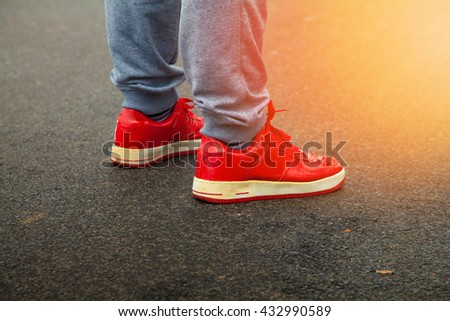 red sneakers are asphalt with sunlight in the frame horizontal photo