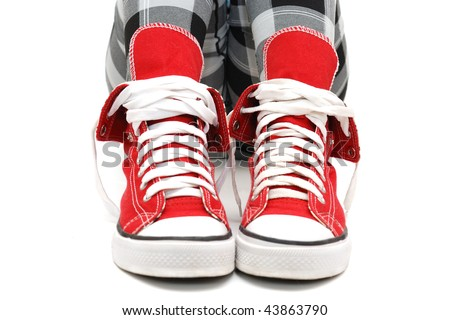 Red sneakers on Girl's feet . Isolated over white.