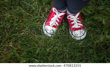 red sneakers on green grass, top view, informal style