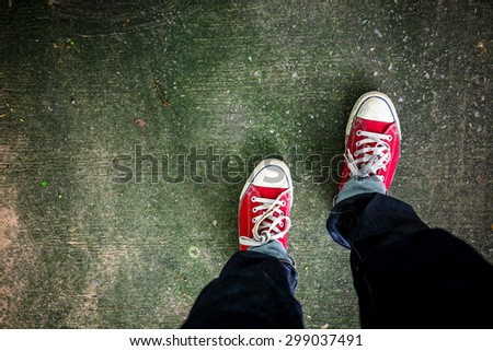 Red Sneakers shoes walking on concrete look top view , Canvas shoes on dirty concrete , Hister life - stock photo
