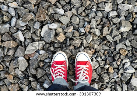 Red Sneakers shoes walking on stone ground , Concept of travel  - stock photo