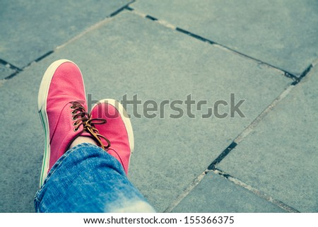 Red sneakers with white sole and blue jeans  - stock photo