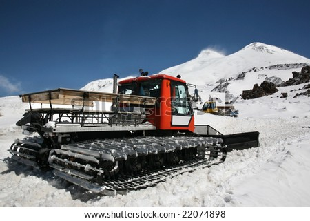 Red snow crawler ready to work with clean blue sky. Mountain Elbrus, Kavkaz in Russia.