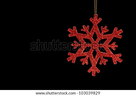 Red snow flake on a black background for Christmas - stock photo