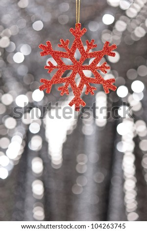 Red snow flake on a silver glitter background for Christmas - stock photo