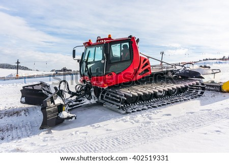 Red snow-grooming machine on snow in Czech mountains