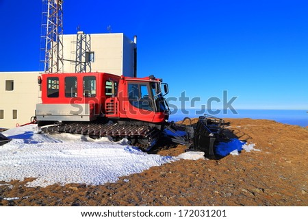 Red snow grooming machine waiting for the snowfall - stock photo