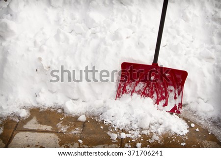 Red snow shovel in a snow bank on pavement - stock photo