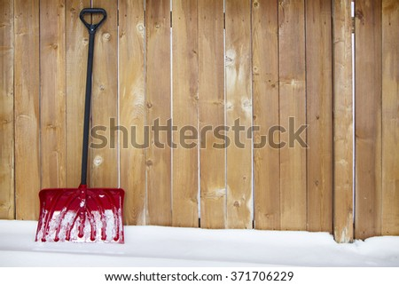 Red snow shovel leaning up against a fence on a snow drift - stock photo