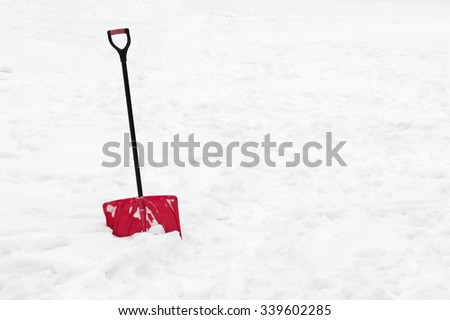 Red snow shovel standing in snow. Winter concept. - stock photo