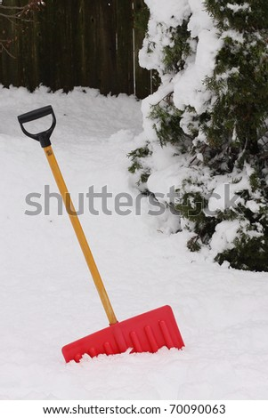 Red snow shovel standing up in deep snow. - stock photo
