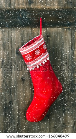 red sock with snowflakes for Santa gifts hanging over rustic wooden background. christmas stocking. vintage style picture with falling snow effect - stock photo