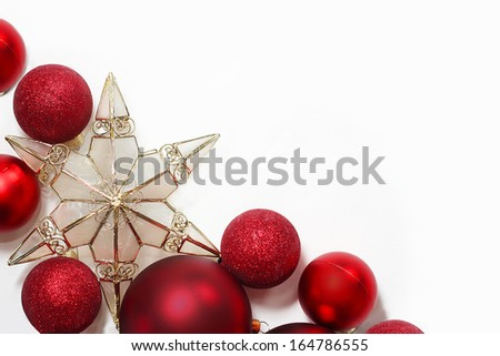 Red sparkly Christmas Bulb Decorations and a gold tree topper star are in the corner framing a white background for text, copy space, or to be used as a Holiday Greeting card. - stock photo