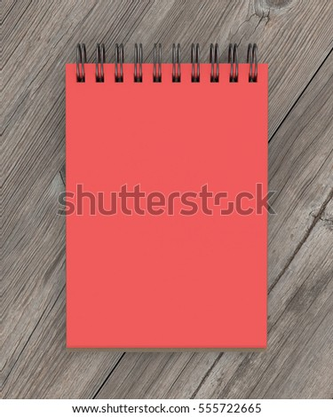 Red spiral notepad isolated on wooden background. Include clipping path of the border of notepad. 3d render