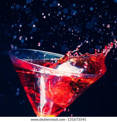 red splashing cocktail on black - stock photo