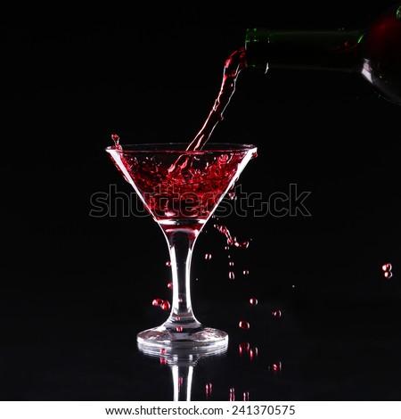 red splashing cocktail on black.  - stock photo