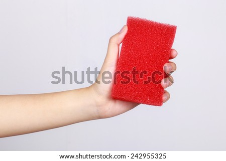 red sponge against with hands cleaning on white background - stock photo