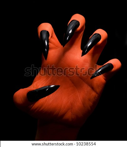 Red spooky devil hand on a dark background catching you - stock photo