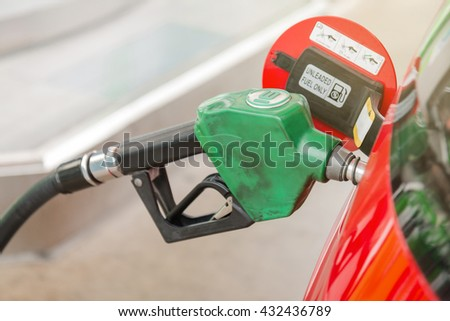 Red sport car refueling on a gas station (Petrol station) - stock photo