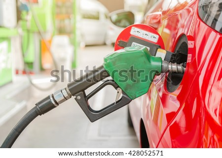 Red sport car refueling on a gas station (Petrol station). (Selective focus and shallow depth of field) - stock photo
