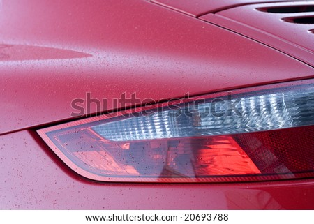 red sports car detail covered with small water drops