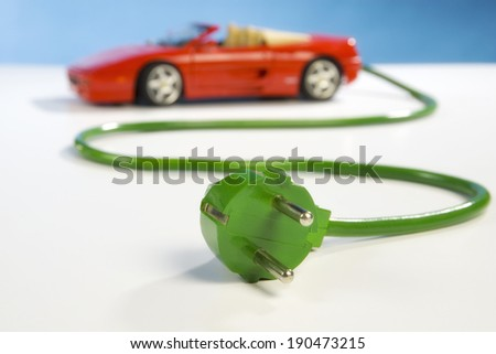 Red sports car, green power cable and plug - stock photo