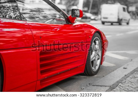 Red sports car on city streets, black and white background - stock photo