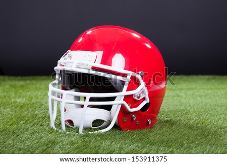Red Sports Helmet Lying On Green Grass Field - stock photo