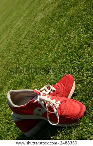 Red sports shoes on a green field - stock photo