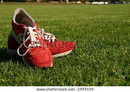 Red sports shoes on a green grass field