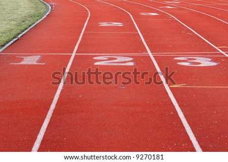 red sports track with white lines and showing numbered starting points