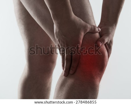 Red spot on painful male knee over light grey background. Man having rheumatism and sprain problem. - stock photo