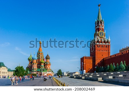 Red Square of Moscow in the summer evening. Red wall of the Kremlin, Spassky (Savior's) tower and St. Basil's cathedral. Soviet era viewing stand (right) to watch civilian and military parades - stock photo