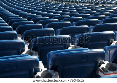 Red staduim seats cast in bright sunshine and shot from behind. - stock photo