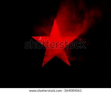 Red Star. Hole cut in cardboard, smoke machine and spotlight.  - stock photo
