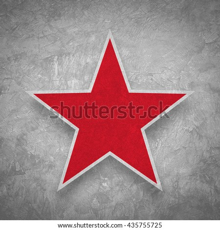 Red star on grunge concrete wall background.