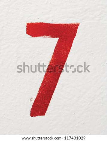 Red stenciled number Seven on old painted wall - stock photo
