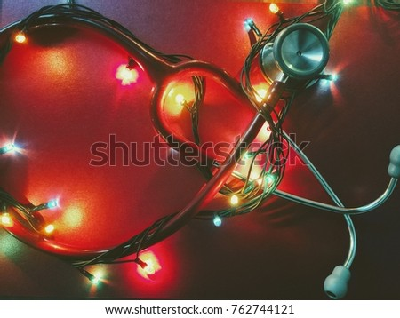 Red Stethoscope And Shining Colorful Christmas Lights Isolated On Background Vintage Toned Medical