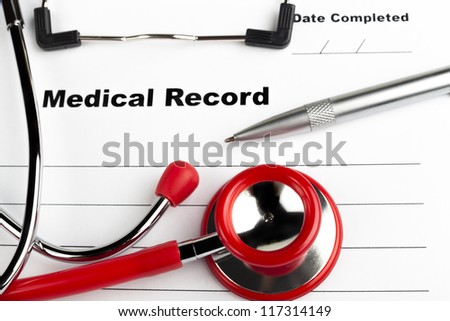 Red stethoscope on  blue clipboard  with medical record close-up with silver colored pen - stock photo