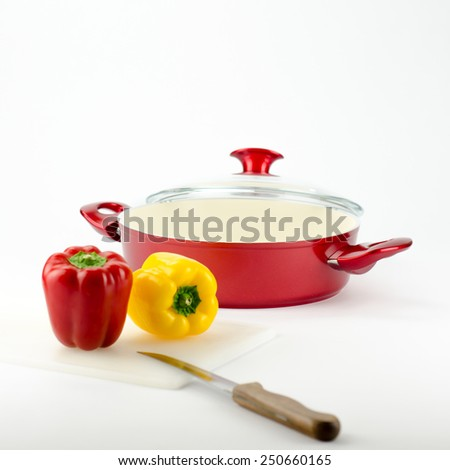 Red stew pot with colourful peppers and a knife near to it.