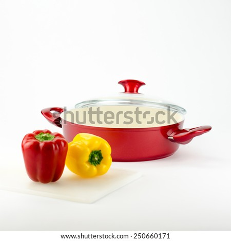 Red stew pot with colourful peppers near to it.