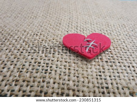 Red stitched broken heart on textured background                                - stock photo