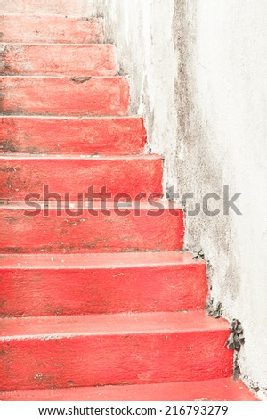 Red stone stairs against a dirty white wall - stock photo