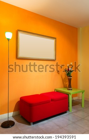 red stool chair, floor lamp, vase on green table and picture frame on orange wall