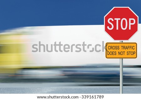 Red stop road sign, motion blurred truck vehicle traffic in background, regulatory warning signage octagon, white octagonal frame, metallic pole post, yellow cross traffic does not stop text signage