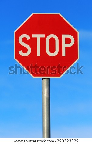 Red stop roadsign against blue sky - stock photo