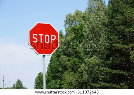 Red stop sign and green trees