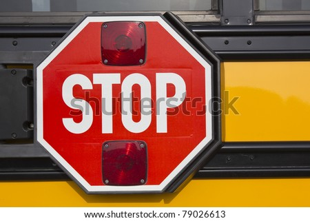 Red stop sign on yellow school bus